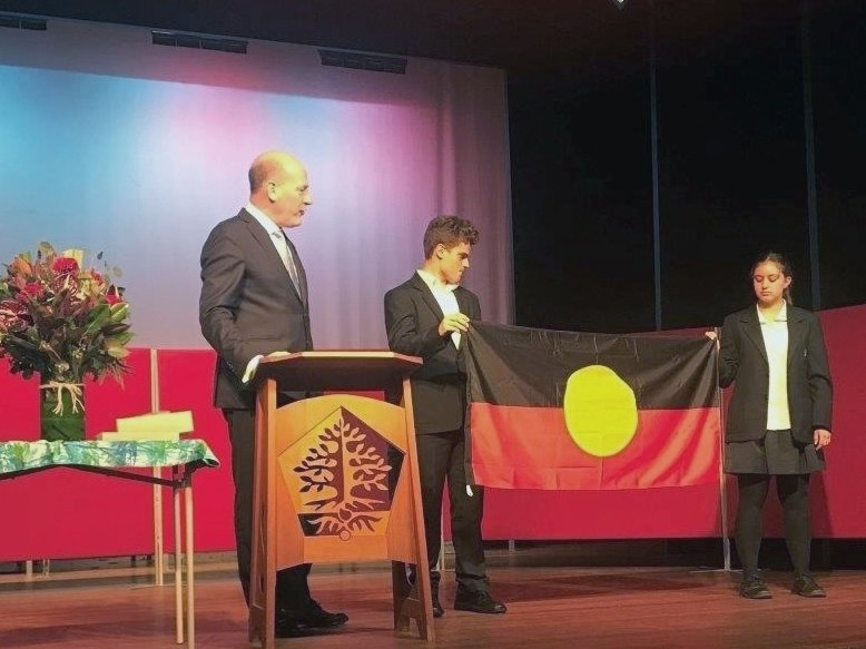 The Aboriginal Flag is presented to Roby Vella and Nelson Whitington-Hall