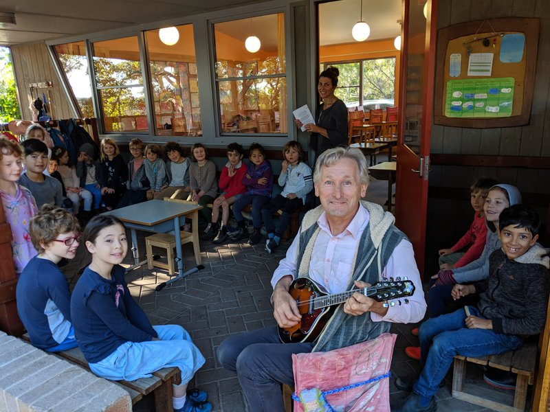 Then the bell rings and Roger brings his class together with songs on his mandolin.